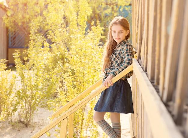 Bella bambina sulle scale della casa di legno