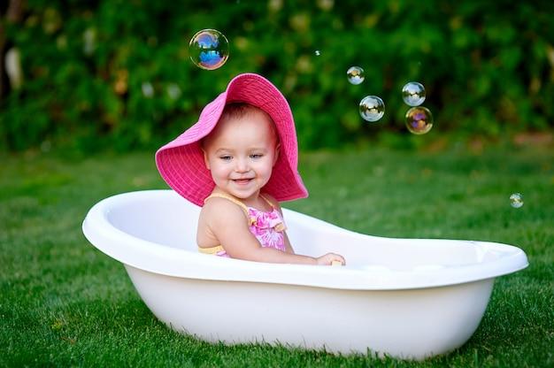 Bella bambina di estate che bagna con le bolle di sapone