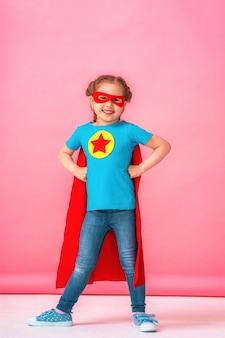 Bella bambina in costume da supereroe in mantello rosso e maschera mostra quanto sia forte