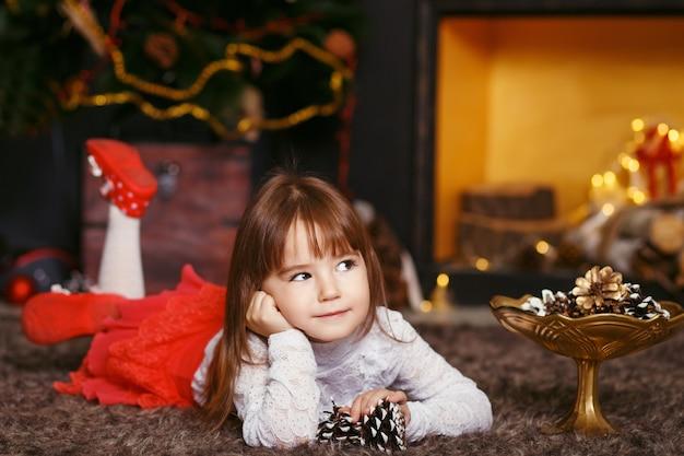 Bella bambina in attesa di un miracolo nelle decorazioni natalizie. preparazione del nuovo anno
