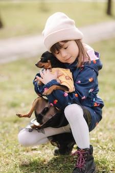 La bella bambina cammina con il cane sveglio all'aperto bambina di sei anni abbraccia il suo animale domestico