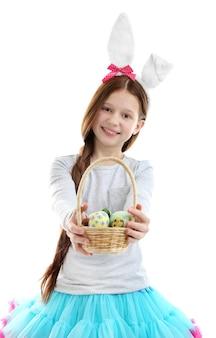 Bellissima bambina che indossa le orecchie del coniglietto pasquale e tiene in mano un cesto di vimini con uova di pasqua, isolate su bianco