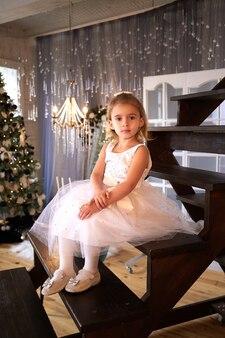 Bella bambina in abito bianco in interni moderni di natale