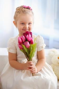 Bella bambina in un vestito bianco che si siede su un davanzale con un mazzo di tulipani rosa