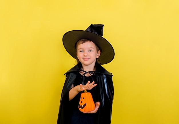Una bella bambina in un costume da strega con una zucca e una scopa su un muro giallo isolato con una copia dello spazio