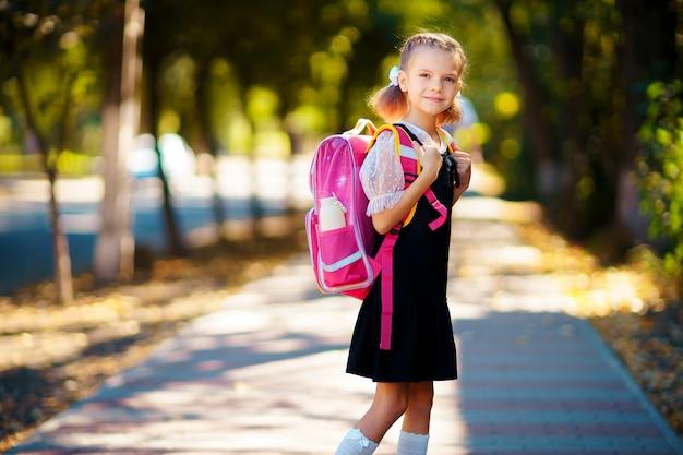 Bella bambina con lo zaino che cammina nel parco