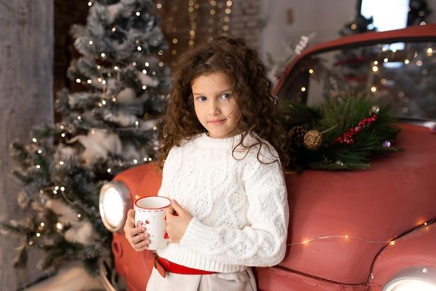 Bella bambina con la tazza di natale vicino all'automobile rossa e agli alberi di natale con le luci. buon natale e buone feste