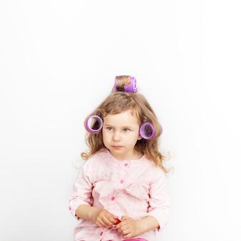 Bella bambina con i bigodini sulla sua testa che guarda l'obbiettivo e divertirsi a casa