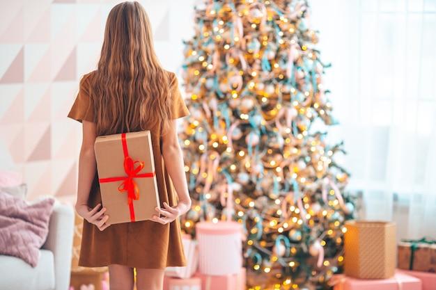 Bella bambina con un regalo. la vista posteriore del bambino tiene una confezione regalo vicino all'albero di natale al chiuso. buon natale e buone feste.