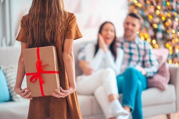 Bella bambina con un regalo. la vista posteriore del bambino tiene una confezione regalo vicino all'albero di natale. i genitori cercano la loro figlia