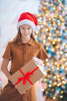 Bella bambina con una confezione regalo vicino all'albero di natale. buon natale e buone feste.