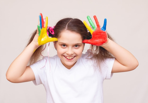 Bella bambina con le mani nella vernice