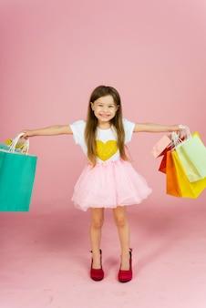 Bella bambina con le borse della spesa