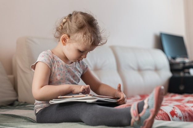 Bella bambina con un tablet, gioca e si siede sul divano di casa. didattica a distanza e un bambino