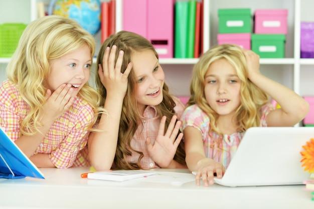 Belle bambine con laptop in classe