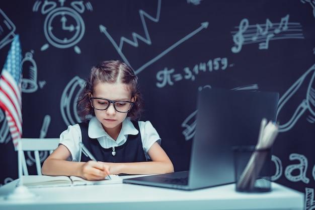 Bella scolaretta seduta alla scrivania e studia online con il computer portatile su sfondo nero con...
