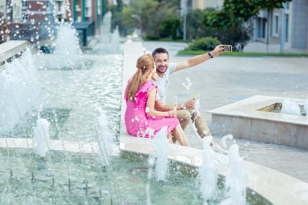 Bella posizione. piacevole giovane coppia seduta insieme vicino alla fontana mentre si scattano selfie lì