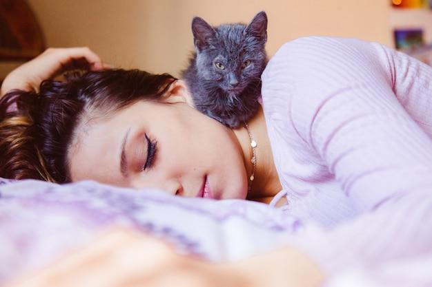 Donna bella solitudine schiacciando un pisolino a casa con il suo gatto. gattino lanuginoso che dorme con la donna stanca.