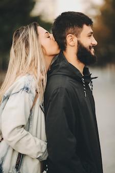 Bella donna bionda capelli lunghi che bacia la testa con gli occhi chiusi del suo ragazzo con amore mentre guarda lontano sorridendo felice mentre si cammina al mattino.