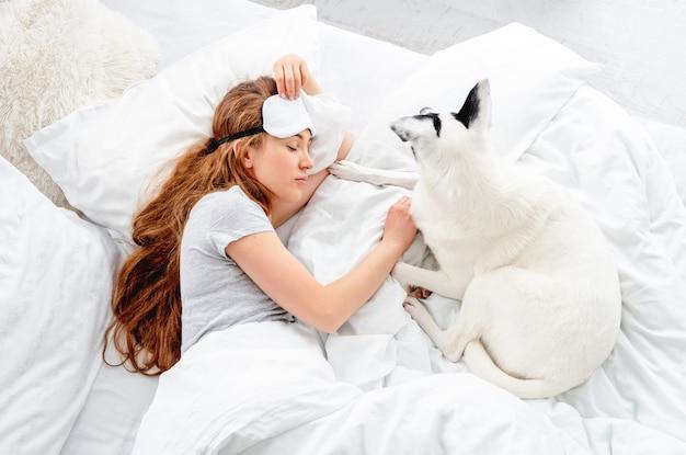 Bella ragazza dai capelli lunghi sdraiata a letto con un cane carino e che dorme. donna abbastanza giovane che riposa con l'animale domestico. persona di sesso femminile che indossa la maschera per dormire sugli occhi che fa un pisolino con il cagnolino