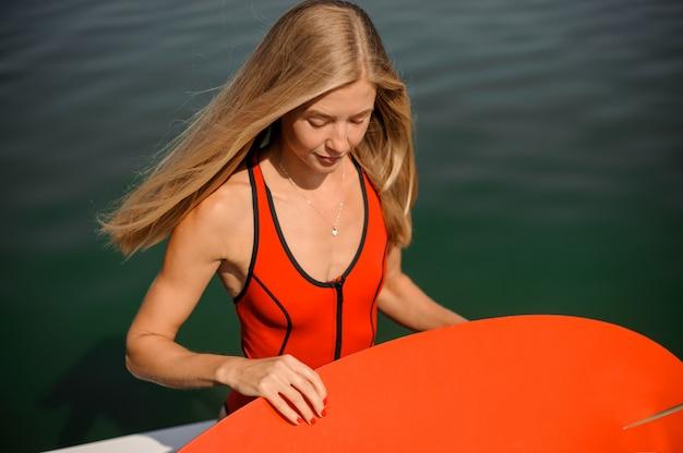 Bella donna bionda dai capelli lunghi che tiene un wake board