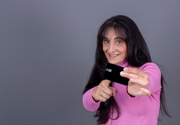 Bella donna bruna dai capelli lunghi sulla quarantina, sorridente e mostrando la sua carta di credito.