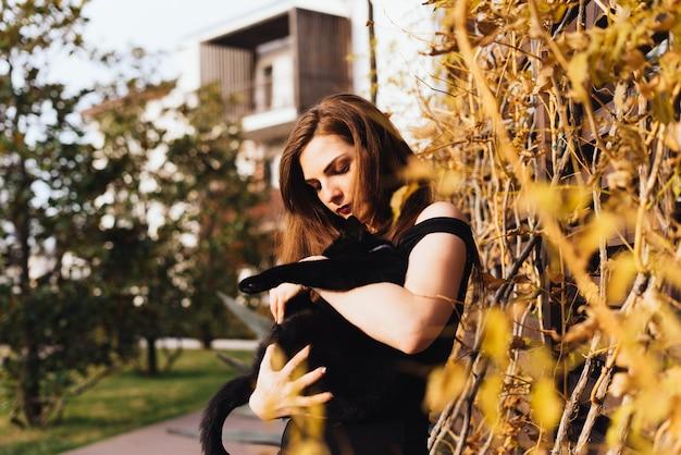 Bella ragazza dai capelli lunghi cammina nel suo giardino, tiene in mano un gatto nero black