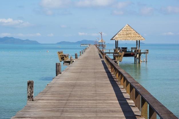 Bellissimo lungo ponte di legno con una capanna all'isola di kohmak in thailandia.