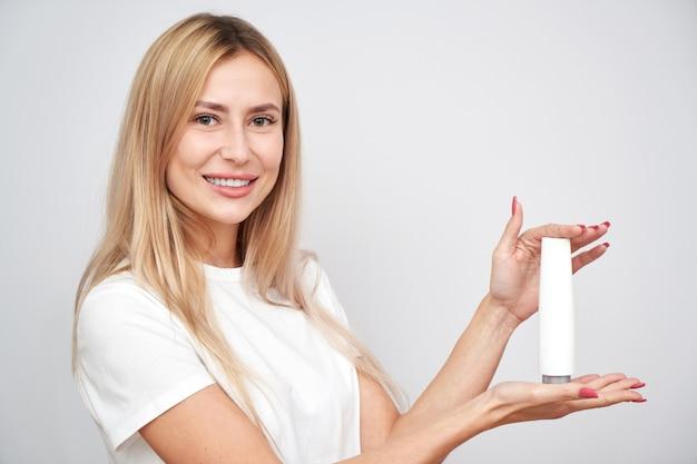 La bella ragazza bionda dai capelli lunghi dimostra il prodotto cosmetico che tiene il corpo di cura della pelle della bottiglia su bianco