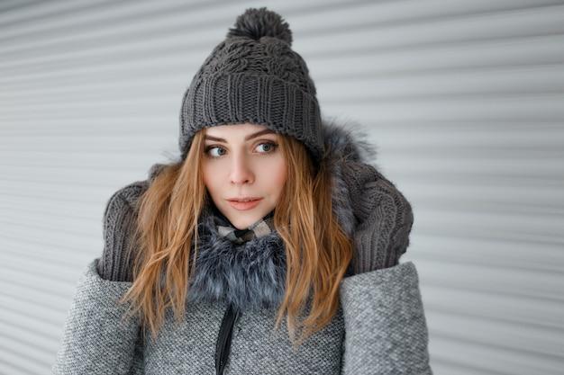 Bella bella giovane donna con gli occhi azzurri in un cappello lavorato a maglia in un cappotto invernale grigio con pelliccia in guanti caldi vintage vicino a un muro di metallo bianco. bella ragazza in una passeggiata.