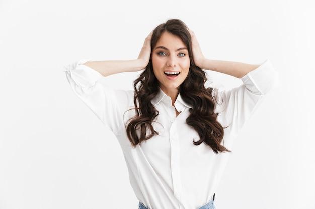 Bella giovane donna adorabile con capelli castani lunghi ricci che indossa una camicia bianca in piedi isolata sopra il muro bianco