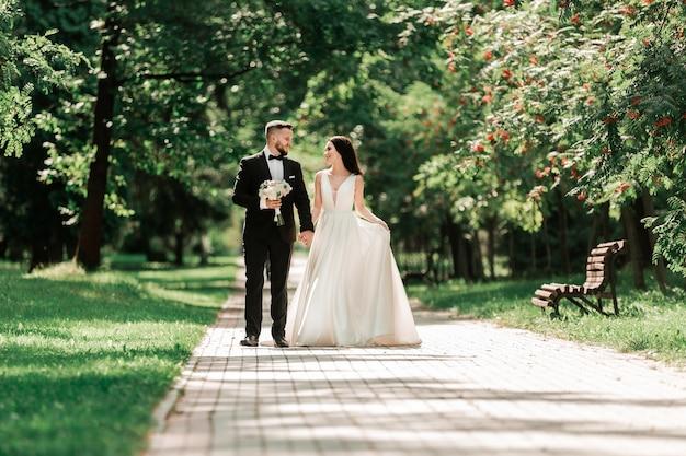 Belle coppie amorose che camminano lungo il sentiero nel parco della città. eventi e tradizioni
