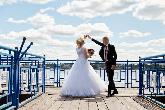 Bella coppia di sposi amorosi registra un matrimonio e cammina lungo il bellissimo lungomare. felicità e amore agli occhi di uomini e donne.
