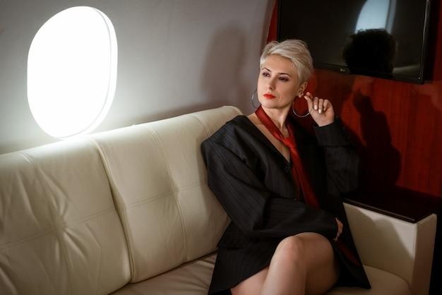 Bella donna lussuosa e sexy in giacca e cravatta rossa su un jet privato