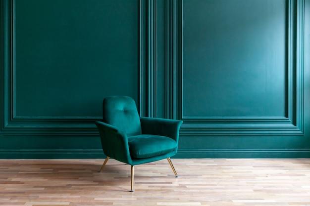 Bella camera interna pulita verde blu classica di lusso in stile classico con poltrona morbida verde. sedia vintage blu-verde antica in piedi accanto al muro color smeraldo. design minimalista per la casa.