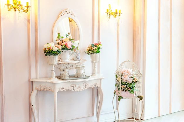 Bella camera da letto interna luminosa bianca classica di lusso bella in stile barocco con grande finestra, poltrona e composizione floreale