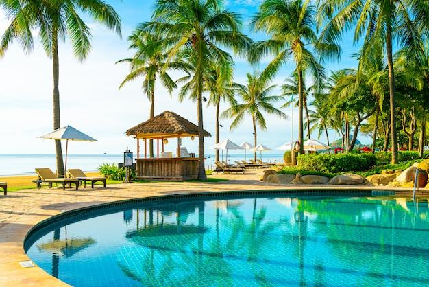 Bei ombrello e sedia di lusso intorno alla piscina all'aperto in hotel e ricorso con l'albero del cocco su cielo blu