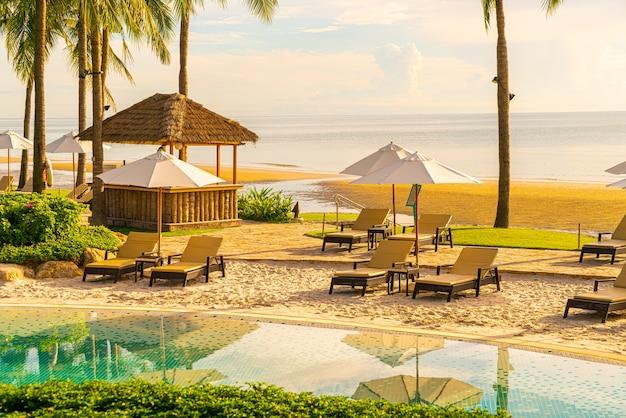 Bellissimo ombrellone e sedia di lusso intorno alla piscina all'aperto in hotel e resort con palma da cocco sul cielo al tramonto o all'alba - concetto di vacanza e vacanza