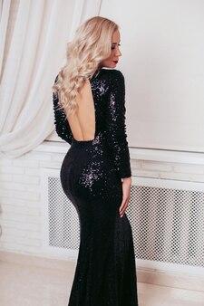 Bella donna di lusso in abito nero scintillante con capelli biondi ricci