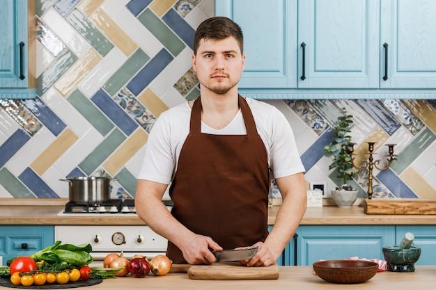 Un bell'uomo che prepara un'insalata a casa in cucina. cucinando.