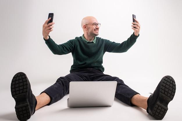 Bello uomo che si siede con il computer portatile e che prende selfie da due smartphone in sue mani.