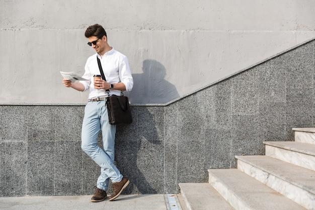 Bellissimo uomo che indossa occhiali da sole bere caffè da asporto e leggere il giornale, stando in piedi lungo il muro all'aperto
