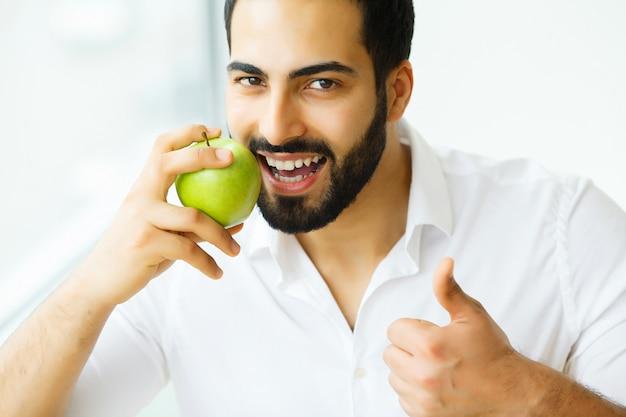 Bello uomo con i denti bianchi che morde la mela