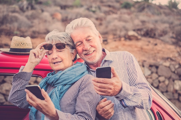 Bello uomo e donna coppia senior maturo uso smartphone all'aperto in attività di svago controllando internet per e-mail e amici da contattare. vacanza e stile di vita. persone che sorridono insieme