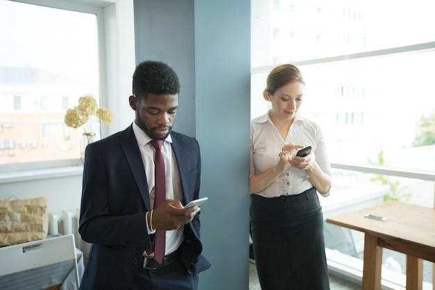 Bello uomo e donna in ufficio con i telefoni cellulari