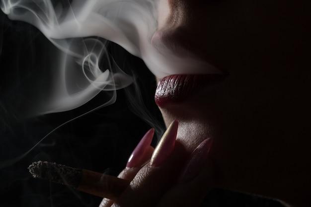 Bella manicure. labbra di sigaretta. fumare sexy. fumare sigaretta. labbra. donna sexy. turbinio di fumo. movimento del fumo. avvicinamento. primo piano del viso.