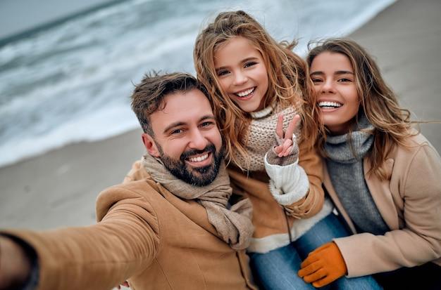 Una bella coppia di sposi e la loro adorabile figlia si abbracciano in riva al mare e si fanno selfie vestiti di palts in inverno.