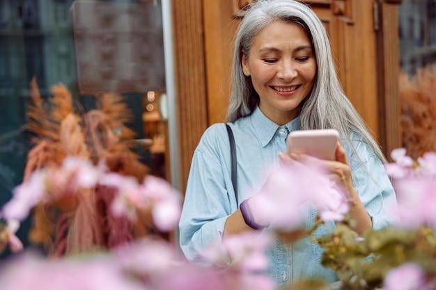 La bella donna asiatica matura in camicia di jeans usa il telefono cellulare sul terrazzo