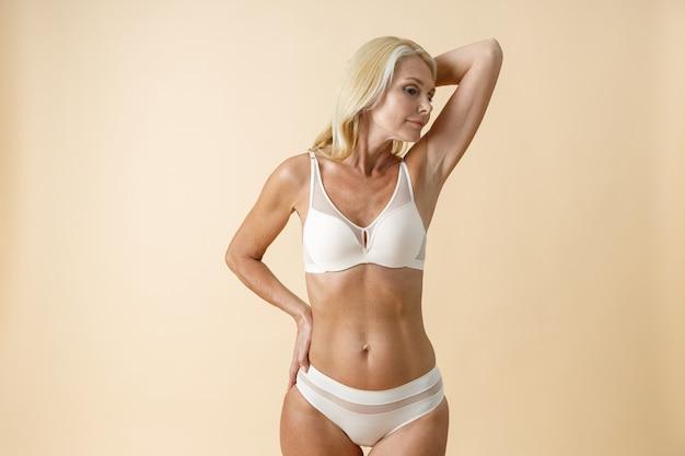 Bella donna bionda matura con una perfetta forma del corpo in biancheria intima bianca che mostra il suo liscio e