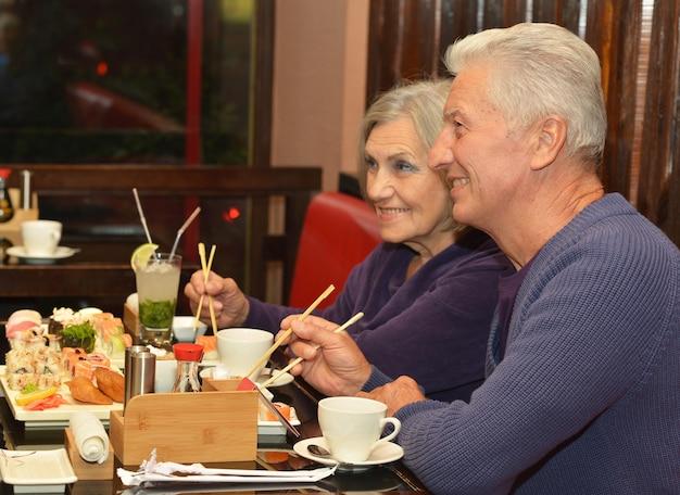 Bella coppia matura che mangia sushi al bar